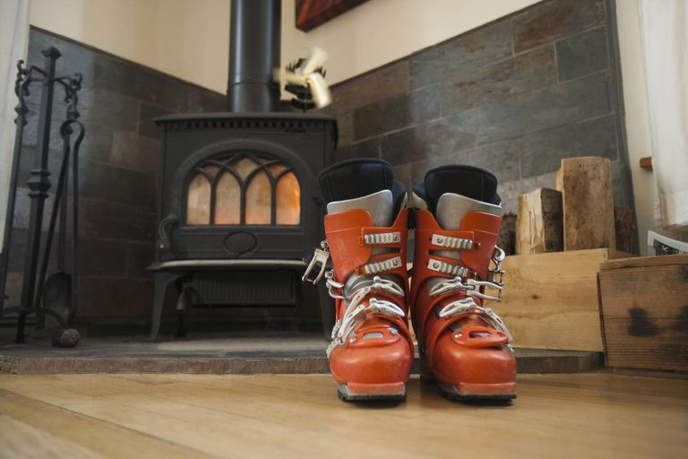 Ski boots drying in front of fireplace