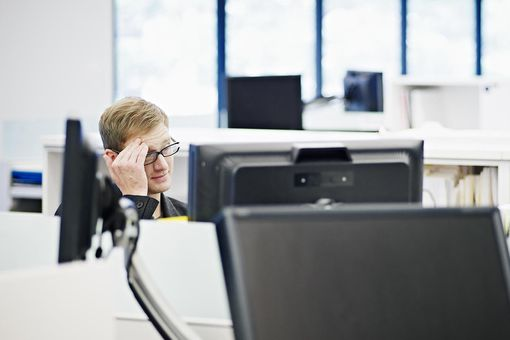 Businessman in office looking at computer monitor