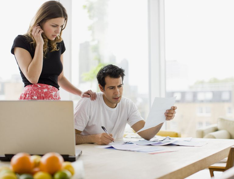 Concerned couple reviewing bills