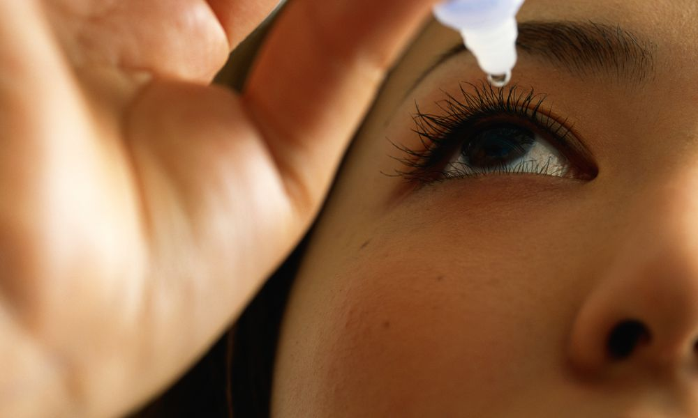 Woman using eye drops, close-up