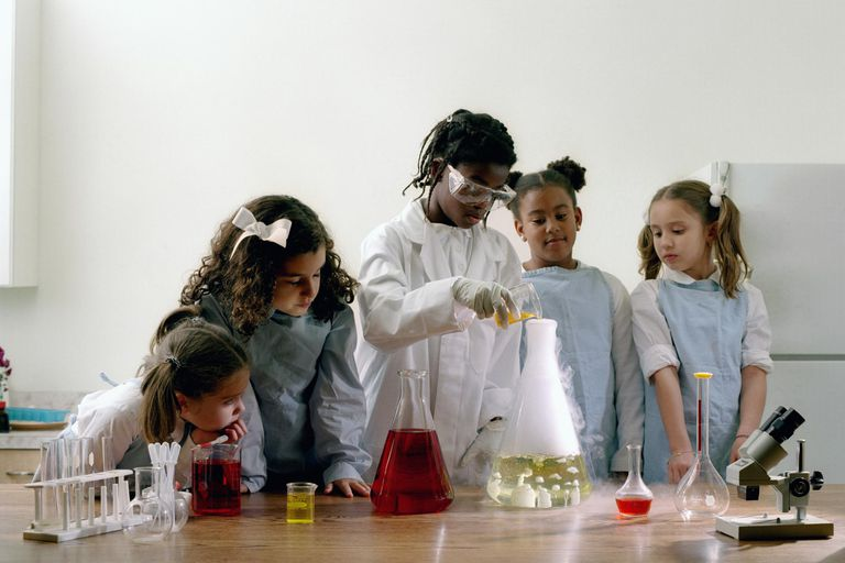 Group of girls (8-10) in science lab working on experiment.