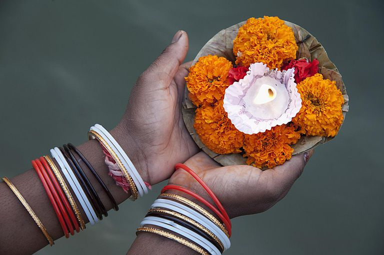 Woman holds a lit butter candle held over Ganges River