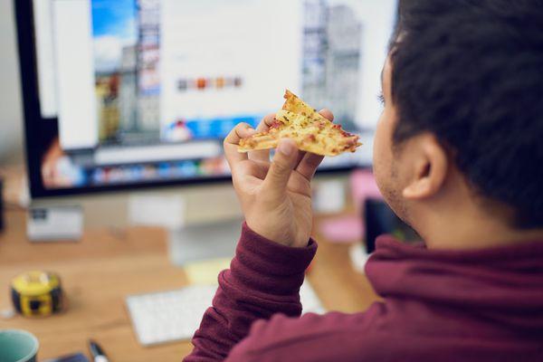 Man eating pizza at his computer