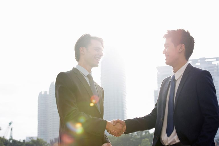 Two businessmen shaking hands outdoors.
