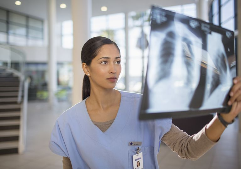 Nurse examining chest x-rays in hospital