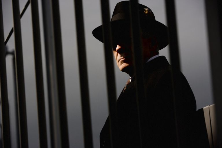 Tough guy looking through steel bars