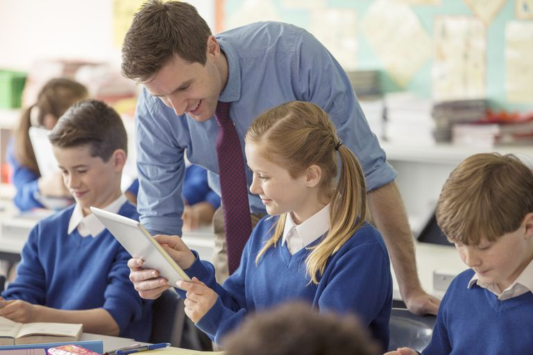 Teacher with his pupils in classroom using tablet pc