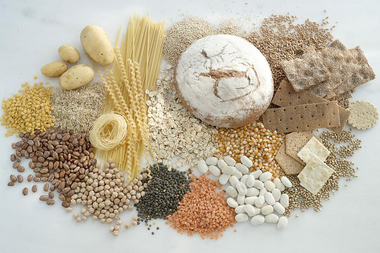 Various foods rich in carbohydrate. Bread, crisp bread,, lentils, beans, potatoes, corn, rice, soya beans, potatoes, pulses, noodles, oat flakes