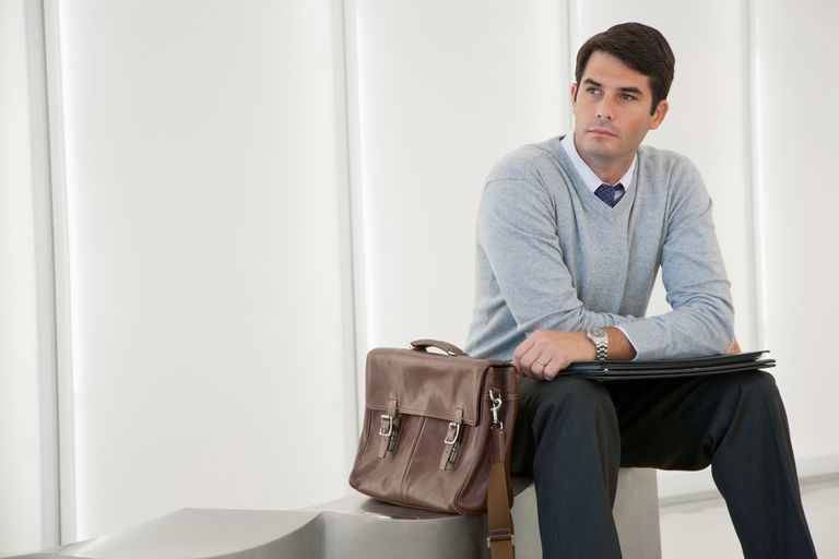 Businessman sitting in office lobby looking at camera