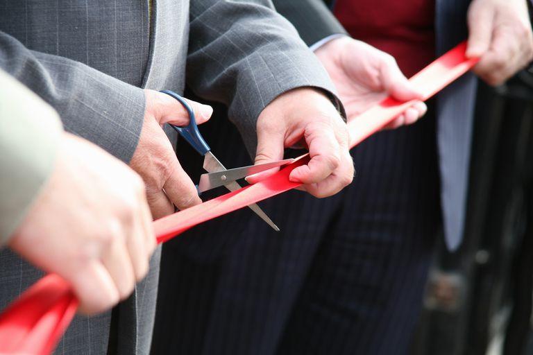Man cutting a ribbon