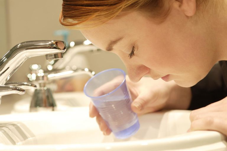 Young woman leaning over bathroom sink, holding glass of water.