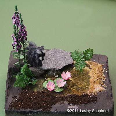 Finished miniature pond in dolls house scale made from E-Z Water set into dry floral foam.
