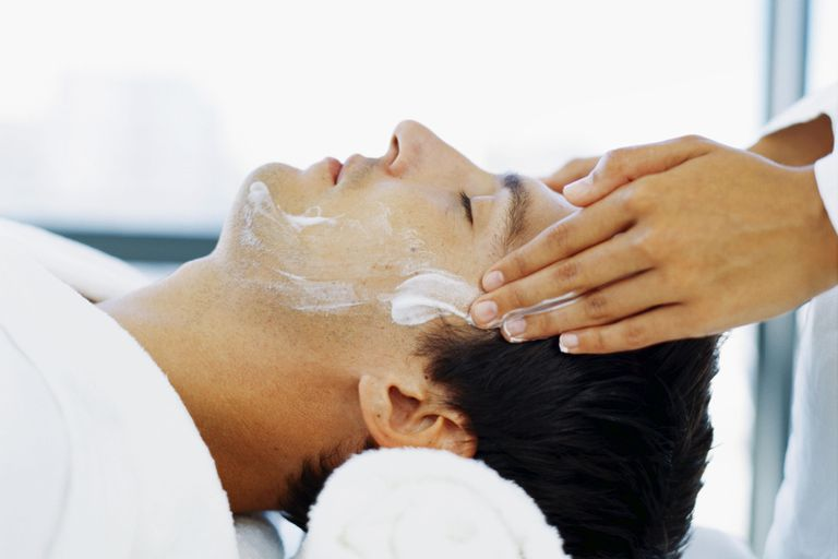Side profile of a young man getting a face massage
