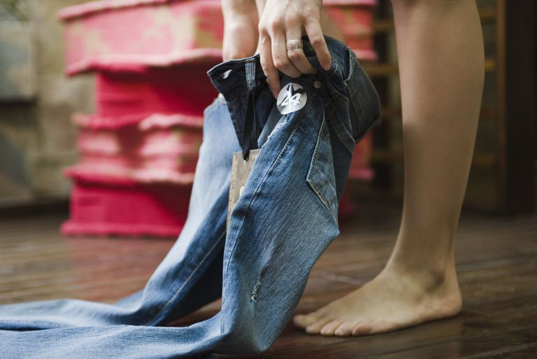 Woman putting on jeans