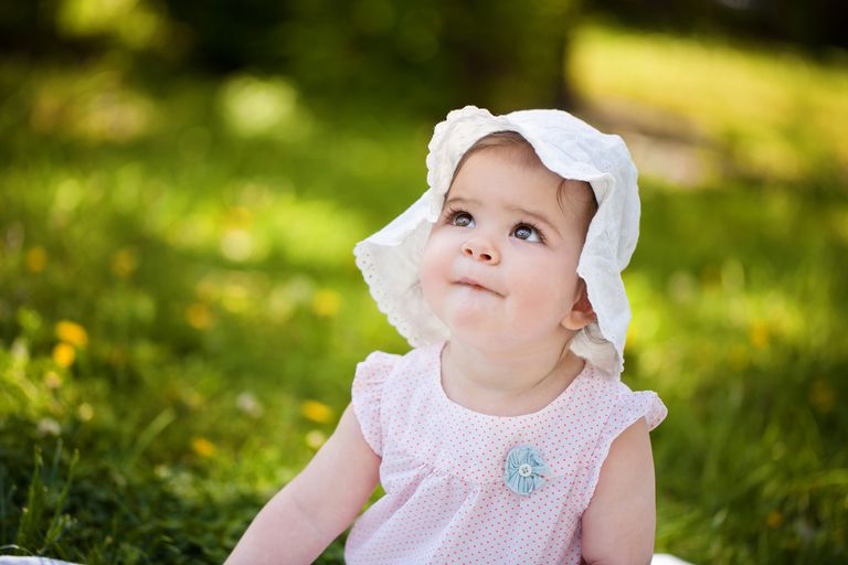 Cute baby girl with hat sitting on the grass.