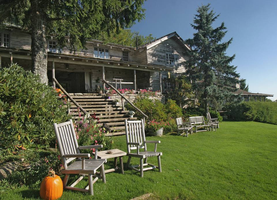 Exterior of country style house with wooden chairs on lawn