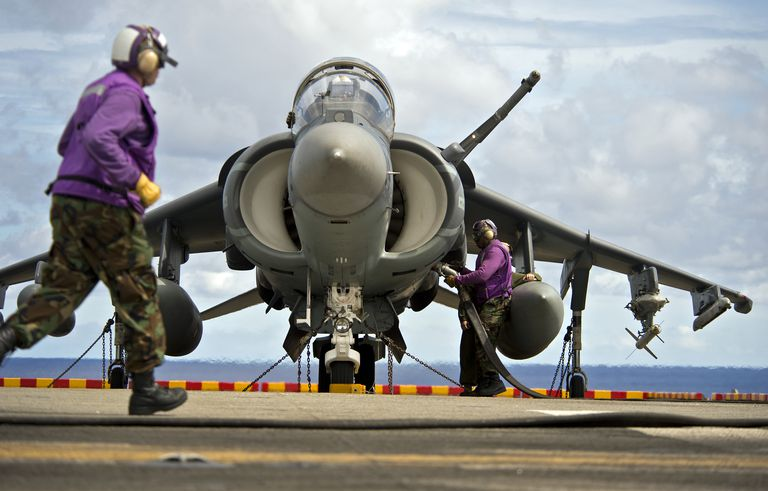 Aviation boatswain's mates refuel an AV-8B Harrier jet aircraft.