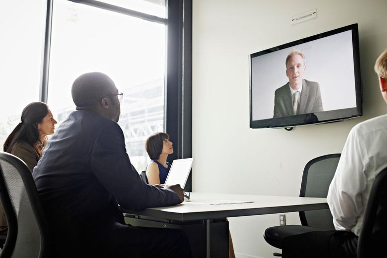 Coworkers in conference room participating in video conference call