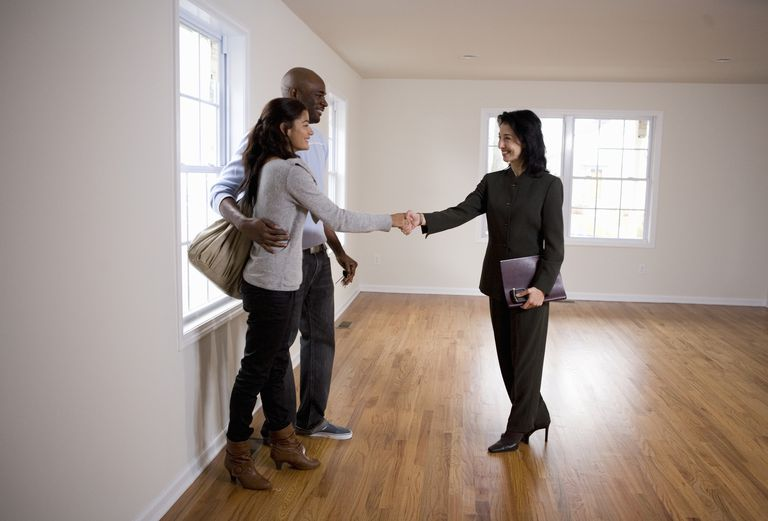 young couple shaking hands with realtor in new home