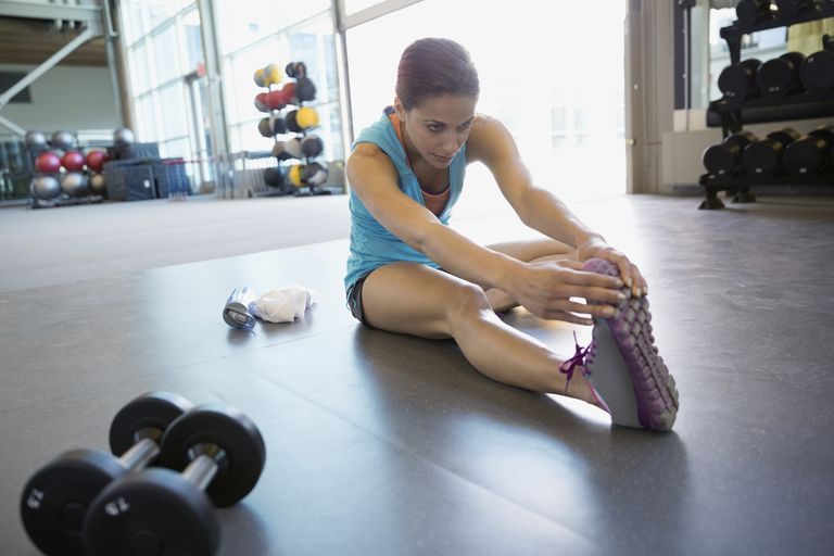 woman sitting on floor in gym stretching her hamstring