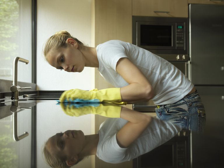 Young woman cleaning kitchen worktop