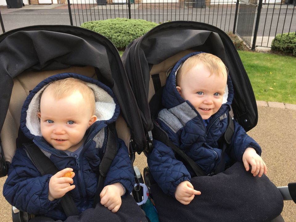 Portrait Of Smiling Twin Brothers Sitting In Baby Carriage At Footpath