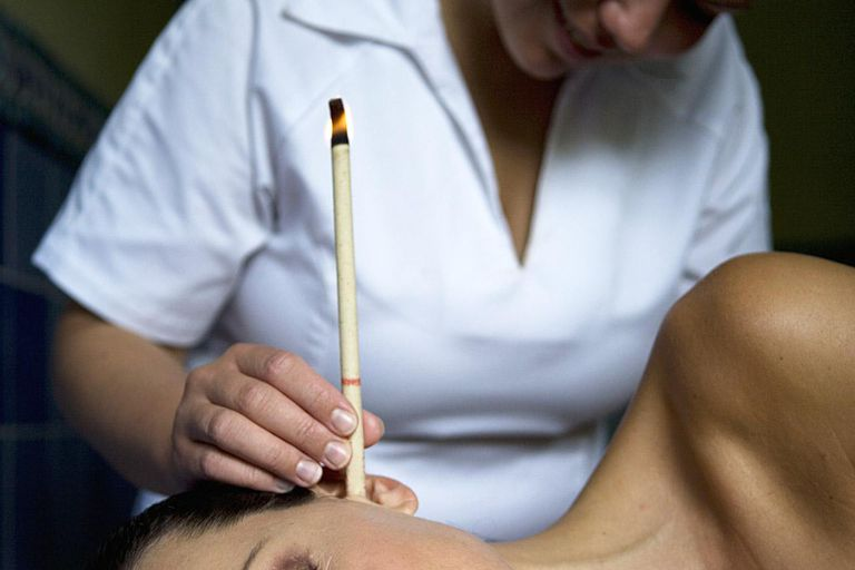 Woman lying downhaving ear candling
