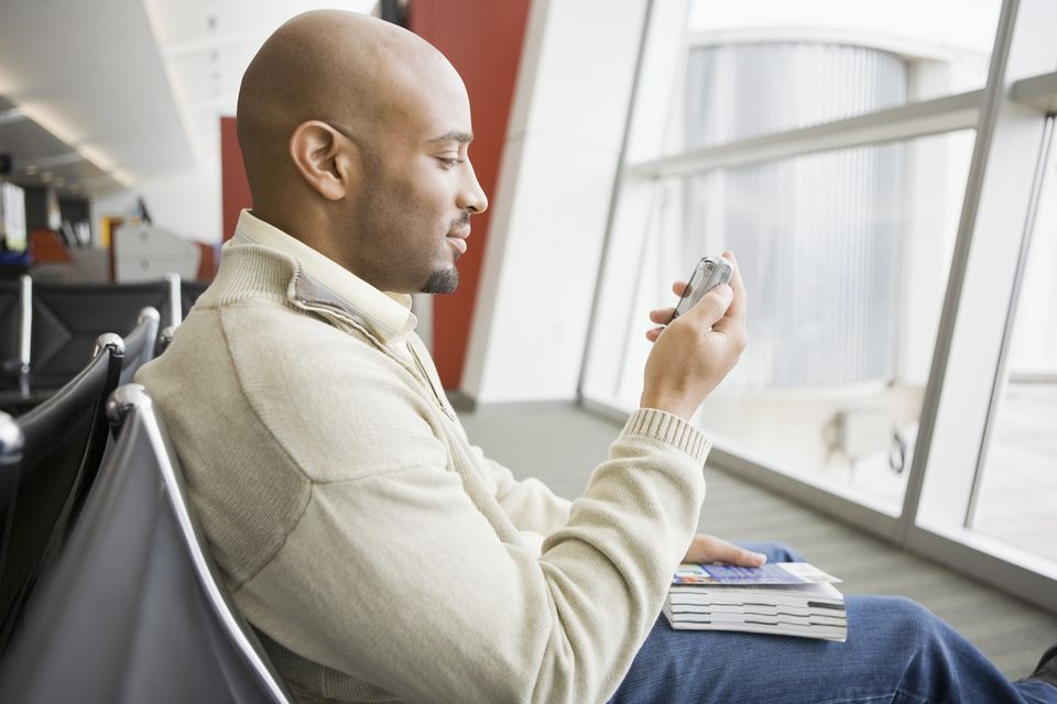 Man using cell phone at airport
