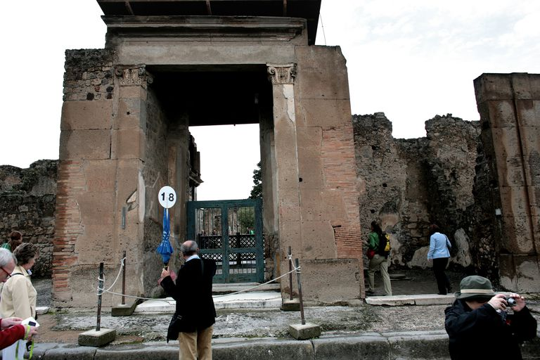 Tour guide and tourists at the entrance to the House of the Faun in Pompeii, ancient Roman city, Italy