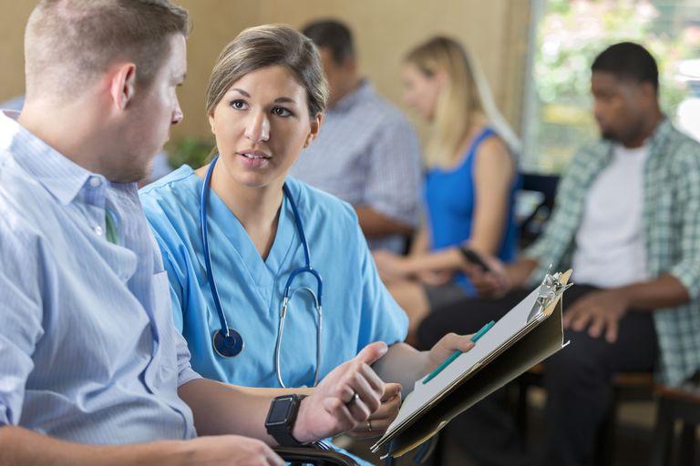 Friendly nurse examining patient in hospital triage center,