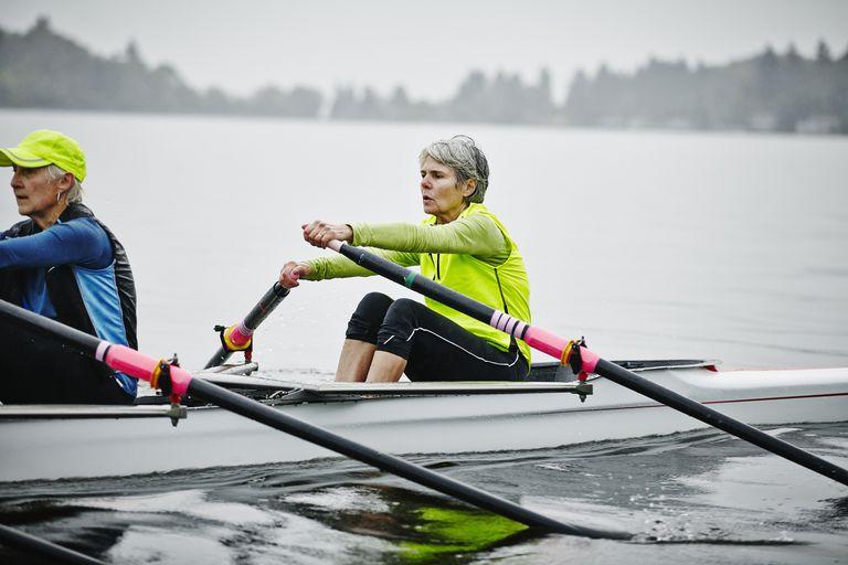 Mature female rowers practicing on rainy morning