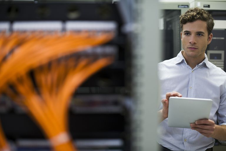 Computer technician using digital tablet performing maintenance