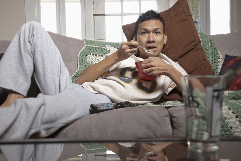Lazy man eating on sofa and watching television