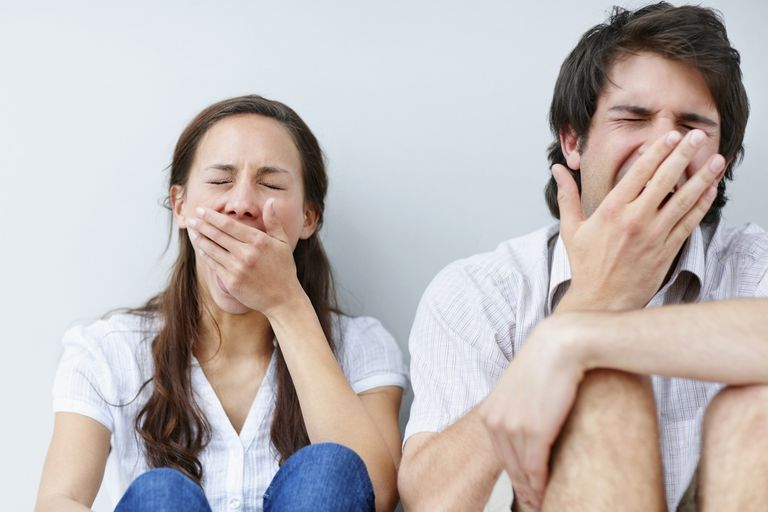 Two people yawn together.