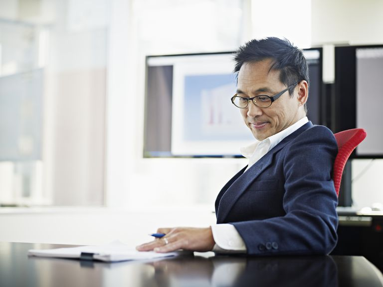 Mature businessman sitting examining documents