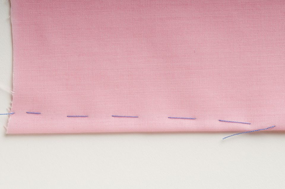 Dart marked out with basting stitch on pink fabric
