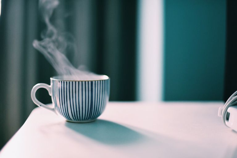 Close-Up Of Steaming Coffee Cup On Table