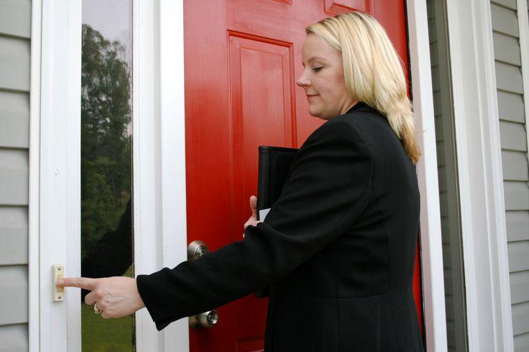 A saleswoman rings a doorbell.