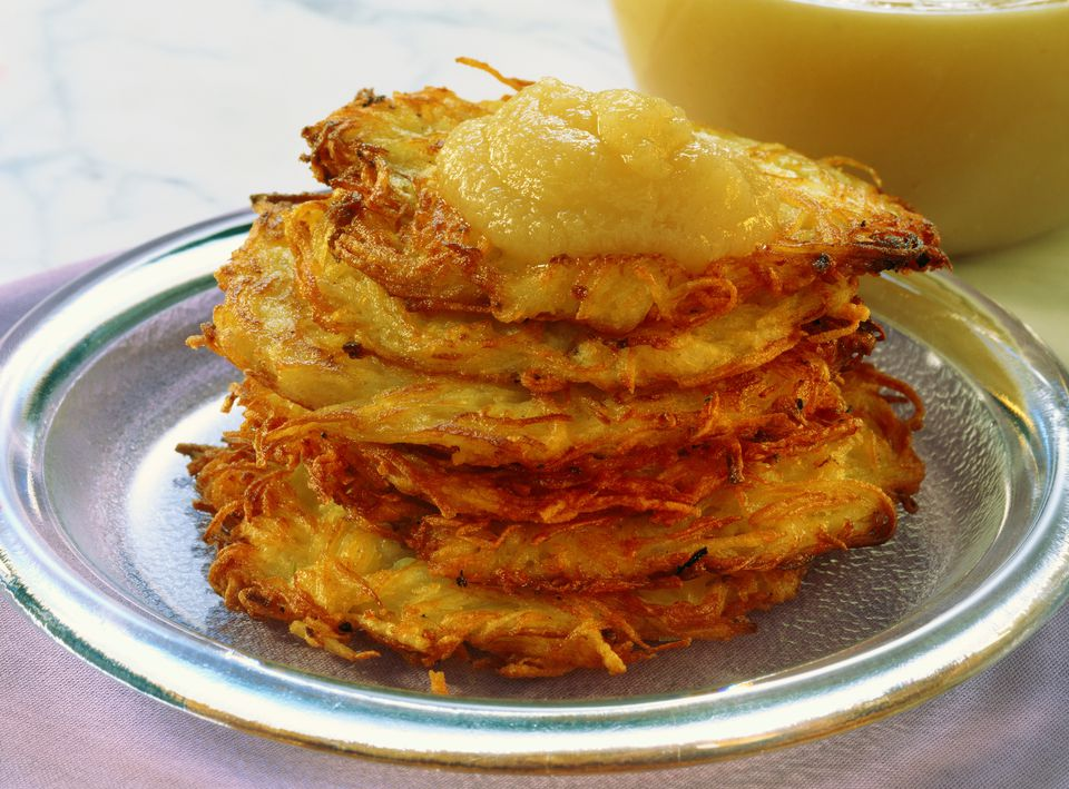 Homemade vegan latkes topped with applesauce