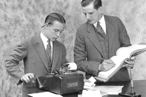 1920s BOOKKEEPER AND YOUNG ASSISTANT IN OFFICE USING LEDGER