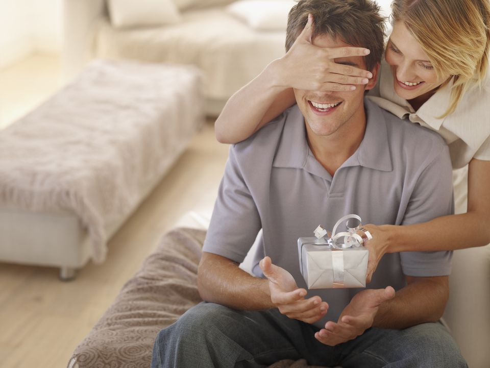 Woman obscuring man's eyes with hand, giving present