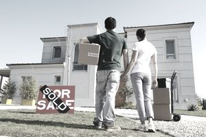 Couple standing in front of newly purchased home