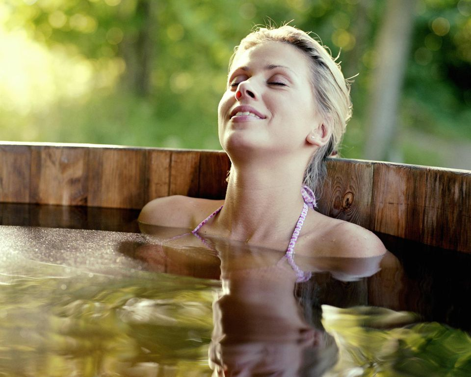 Young woman relaxing in outdoor hot tub, eyes closed, smiling