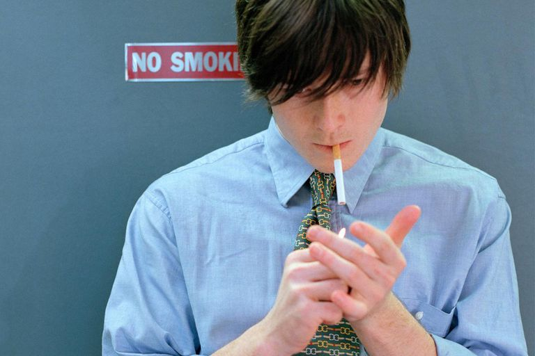 Businessman lighting cigarette in front of 'no smoking' sign