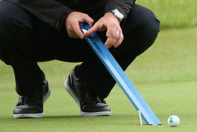 Tournament officials rolls golf ball down Stimpmeter to measure the green speeds