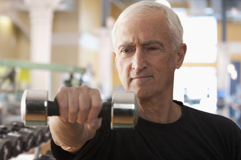 Senior man doing single arm dumbbell raise