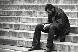 Homeless man sitting on steps in Kiev, Ukraine
