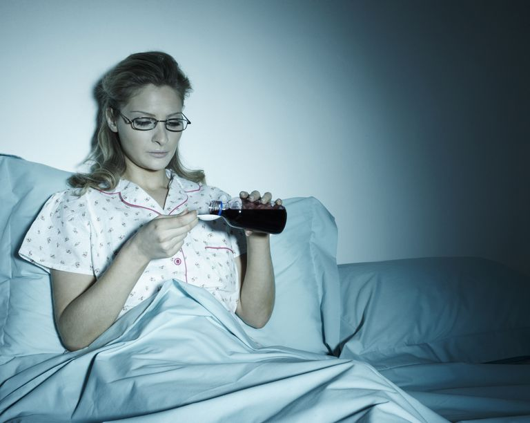 Woman taking cough medicine in bed