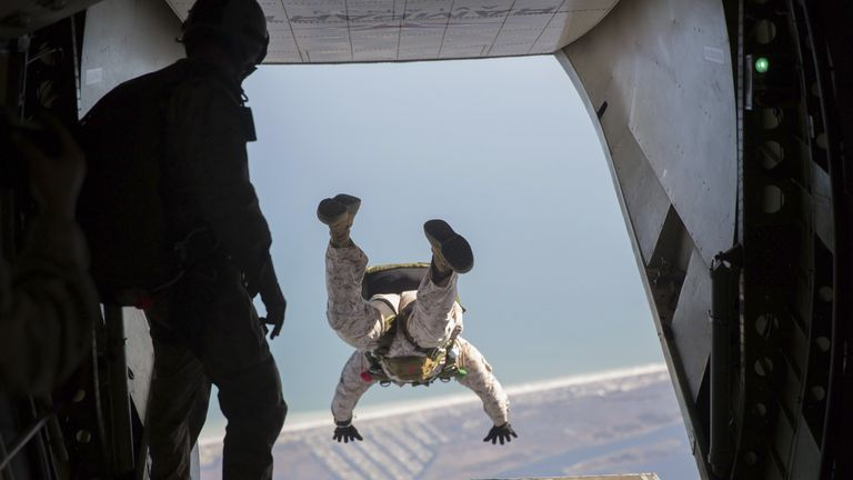U.S. Marine jumps out the back of an aircraft.