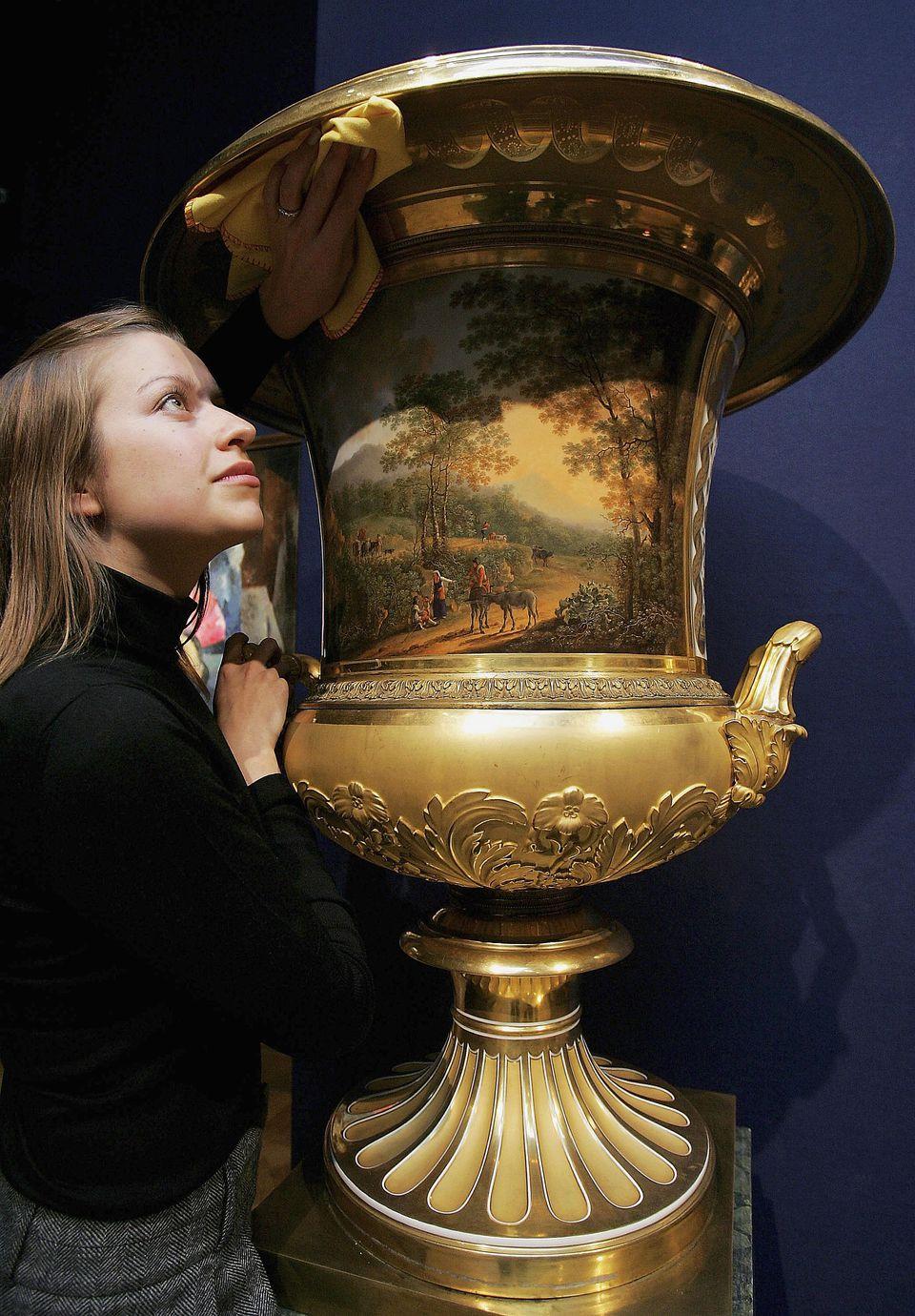 Christie's London employee, Sandra Nedvetskaia, cleans a two-handled Campana vase.